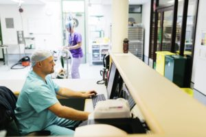 Technician sitting in front of a computer in a hospital.